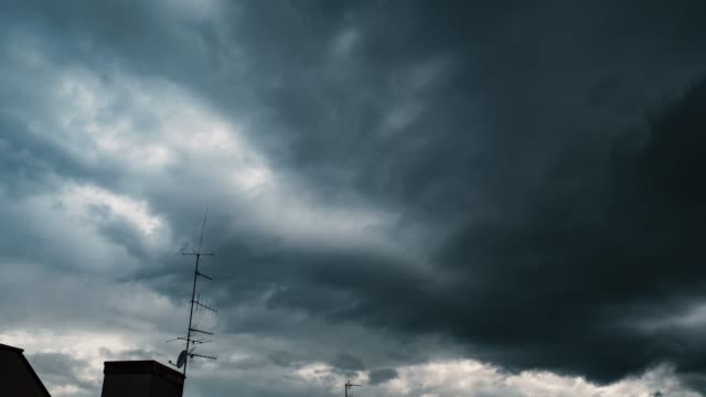 a time lapse of dark swirling storm clouds pass over rooftops. - stratus stock videos & royalty-free footage