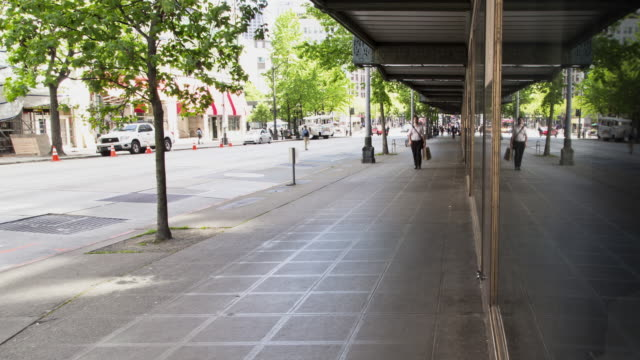 Time lapse of daytime foot traffic moving down a wide, tree-lined sidewalk in downtown Seattle, with car traffic in the background