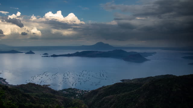 time lapse of dramatic clouds over lake taal and volcano island - batangas province stock videos and b-roll footage