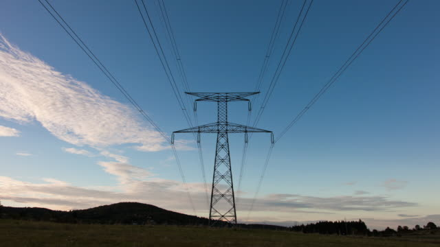vídeos de stock, filmes e b-roll de time lapse of electrical pylon at sunset - alta voltagem