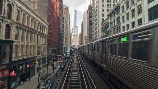 4k time lapse of elevated train tracks are running above the railroad tracks between the building at the loop line at chicago, illinois, usa - subway station stock videos & royalty-free footage