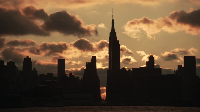 time lapse of empire state building and 34th street silhouette across the hudson river as the sun rises behind the manhattan skyline and clouds pass overhead - 34th street stock videos & royalty-free footage