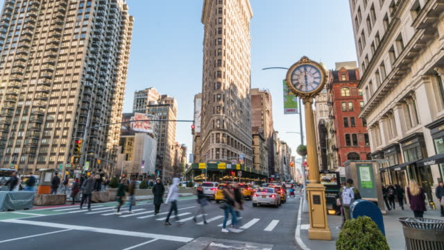4k time lapse of flatiron building with pedestrians and traffic road intersection in rush hour among modern buildings, manhattan, new york city, united states. business and transportation concept - broadway manhattan video stock e b–roll