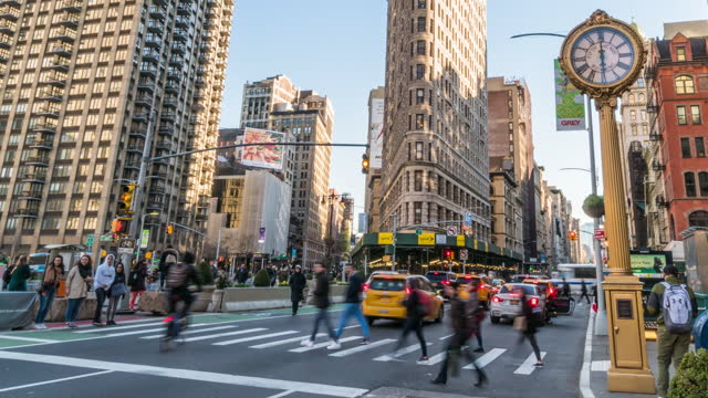 time lapse of flatiron building with pedestrians and traffic road intersection in rush hour, manhattan, new york city, united states - broadway manhattan stock videos & royalty-free footage
