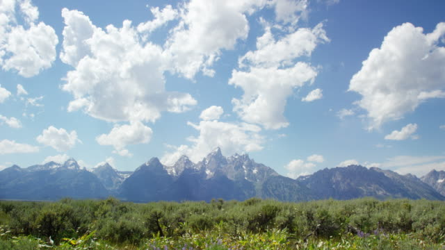time lapse of fluffy white clouds rolling over the grand teton mountains in grand teton national park in western wyoming on a sunny day - grand teton stock videos & royalty-free footage