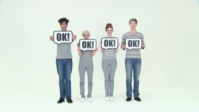 Time lapse of four people with signs that say ok