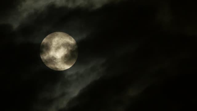 vídeos de stock, filmes e b-roll de time lapse of full moon at nights. blue and dark sky with clouds. - espaço e astronomia