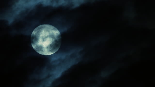 time lapse of full moon at nights. blue and dark sky with clouds. - full moon stock videos & royalty-free footage