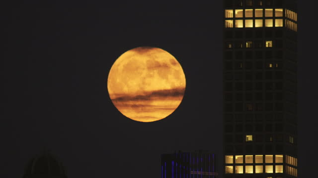 vídeos de stock, filmes e b-roll de time lapse of full moon rising next to 432 park avenue - céu dramático
