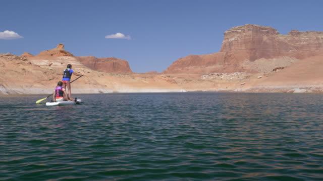 Time lapse of girls on paddleboard in desert lake / Lake Powell, Arizona, United States