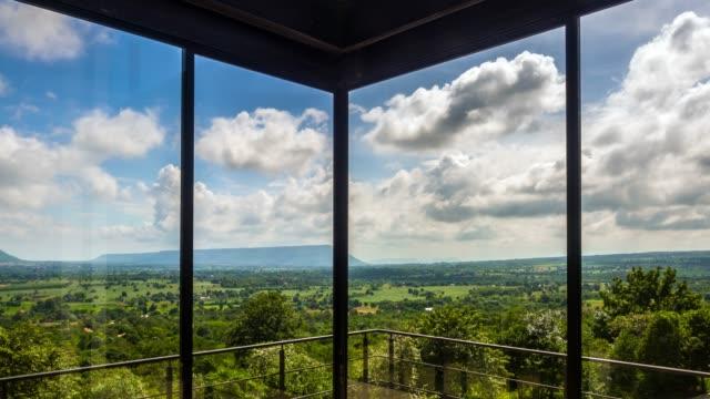 vídeos de stock, filmes e b-roll de lapso de tempo de grandes nuvens passando com janelas modernas em primeiro plano - armação de janela