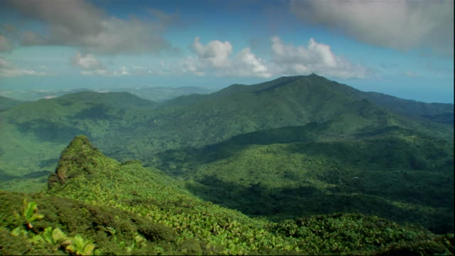 Time lapse of green Luquillo Mountains white clouds in blue sky passing overhead some passing frame