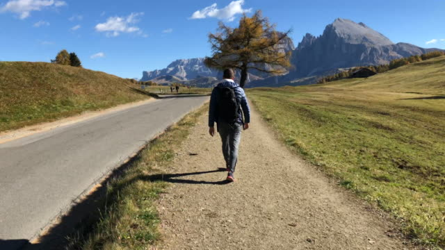 time lapse of guy walking in footpath visiting the alpe di siusi dolomites mountains. - alpe di siusi video stock e b–roll