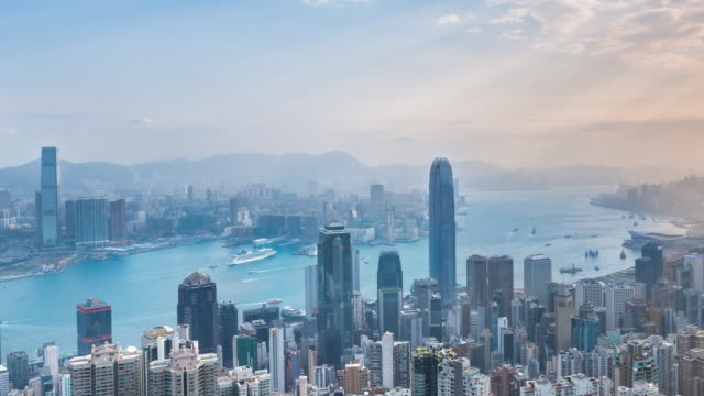 Time Lapse of Hong Kong skyline and Victoria harbor bathed in early morning sunlight, zoom in
