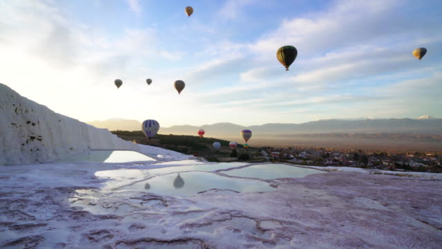 time lapse of hot air balloons in travertine pools limestone terraces at sunrise in pamukkale, denizli - standing water stock videos & royalty-free footage