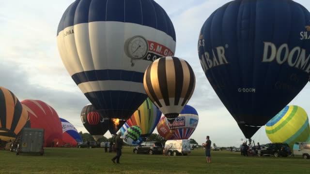 vídeos de stock, filmes e b-roll de time lapse of hot air balloons take to the skies at a preview flight to launch next week's bristol international balloon fiesta on august 5 2016 in... - festa do balão de ar quente