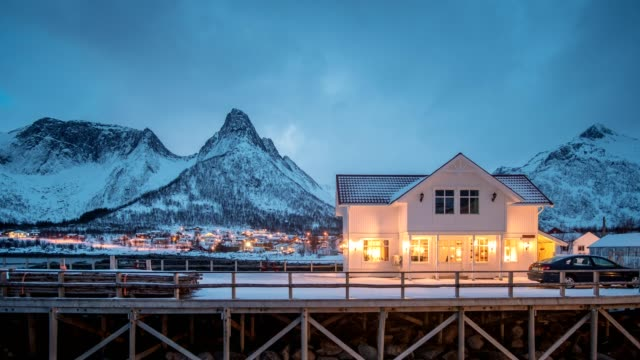 time lapse of house on fishing village glowing with mountain at dusk - heat stock videos & royalty-free footage