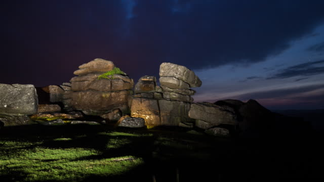 time lapse of illuminated rock formations in dartmoor national park at night - geology stock videos & royalty-free footage