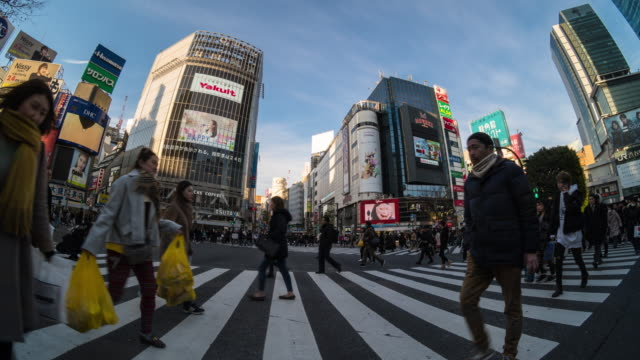 4k time lapse of japanese and foreign tourists are walking across the crosswalk in evening at shibuya district area, tokyo, japan, japanese culture concept - zebra crossing stock videos & royalty-free footage