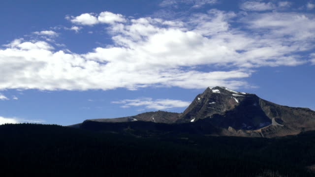 vídeos de stock, filmes e b-roll de time lapse of lone jagged mountain peak with clouds. - glacier national park us