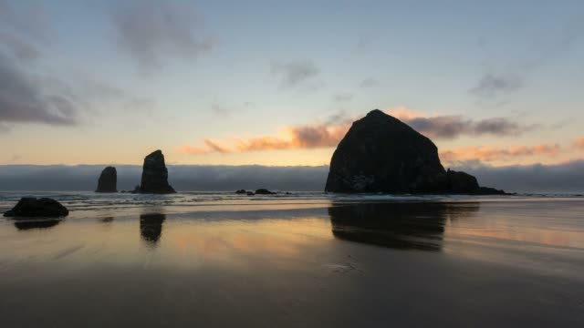 time lapse of low cloud along pacific ocean in cannon beach lowtide at sunset into evening with beautiful reflection of haystack rock - haystack rock stock videos & royalty-free footage