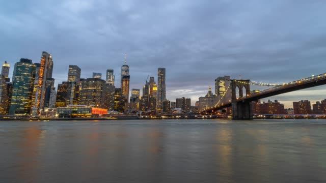 より低いマンハッタンのフィナンシャル・ディストリクト都市景観川沿いの4k 時間経過、ブルックリン・ブリッジとイーストリバーの夜の時間、ニューヨーク市、アメリカ合衆国、建築とラ� - マンハッタン橋点の映像素材/bロール