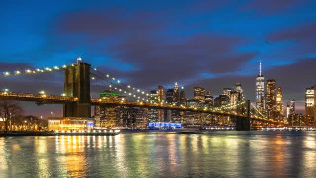 日没時間と昼から夜のシーン、ニューヨーク、アメリカ、建築とランドマークのコンセプトでブルックリン橋と下部マンハッタン金融街の街並み川側の4kタイムラプス - ブルックリン橋点の映像素材/bロール