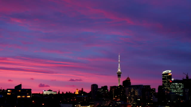 Time lapse of magenta-hued clouds passing over Auckland skyline at sunset / New Zealand