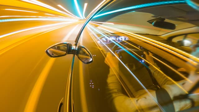 time lapse of man driving car at night on highway - headlight stock videos & royalty-free footage