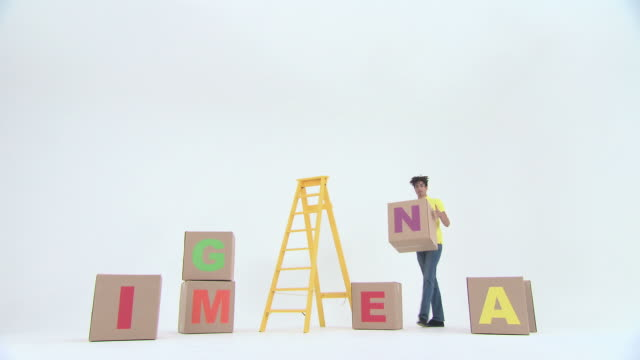 Time lapse of man stacking boxes with letters to spell word imagine