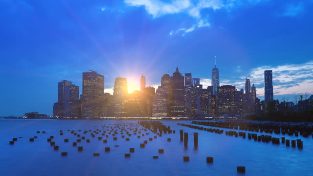 Time Lapse of Manhattan financial district skyline and pilings at sunset