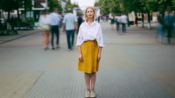 Time lapse of mature woman standing in city in busy street looking at camera