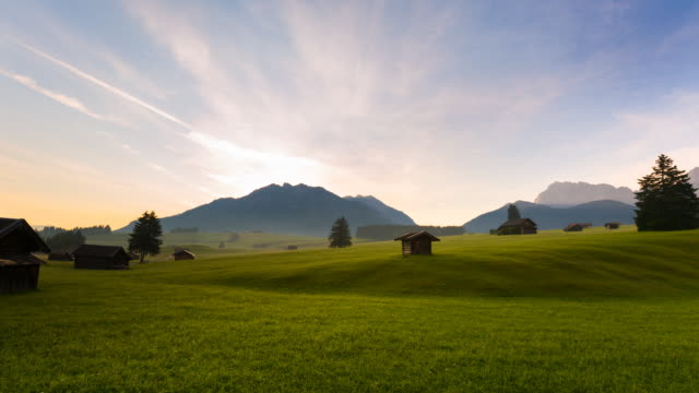 Time Lapse of meadows dotted with hay barns at sunrise