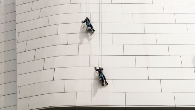 time lapse of men reppelling while cleaning outside of modern building - abseiling stock videos & royalty-free footage