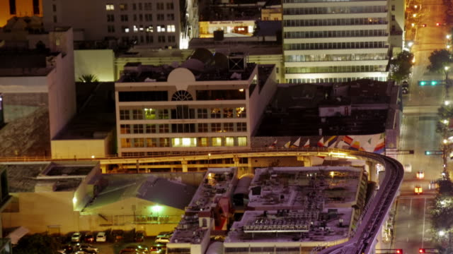 vídeos de stock e filmes b-roll de time lapse of miami downtown at night from above. medium shot with rooftops, traffic and metromover - comboio elevado