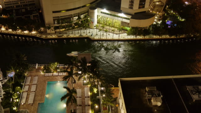 time lapse of miami river at night from above. boat passing, palm trees, swimming pool - spoonfilm stock-videos und b-roll-filmmaterial