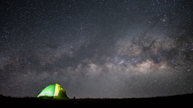 time lapse of milky way and star with galaxy on the sky at night time with tent camping on the mountain - tenda da campeggio video stock e b–roll