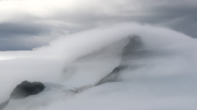 time lapse of mist swirling around snowcapped mountains - clima polare video stock e b–roll