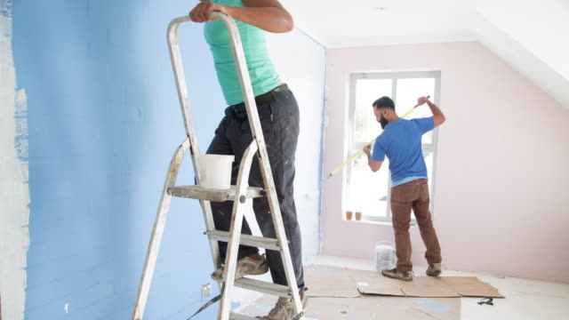 time lapse of mixed race couple painting their home - renovierung themengebiet stock-videos und b-roll-filmmaterial