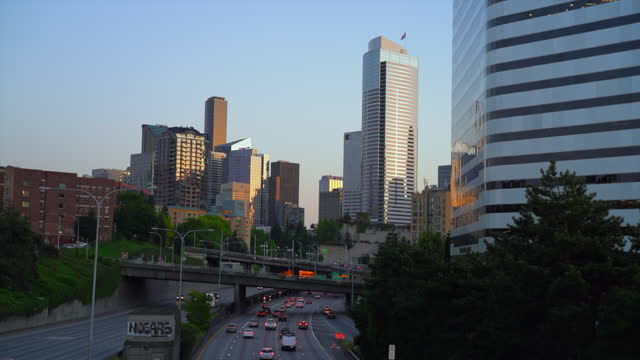 time lapse of moderate highway traffic on the i-5 express with a crystal clear blue sky and a warm light from a setting sun - seattle, washington - fast motion stock videos & royalty-free footage