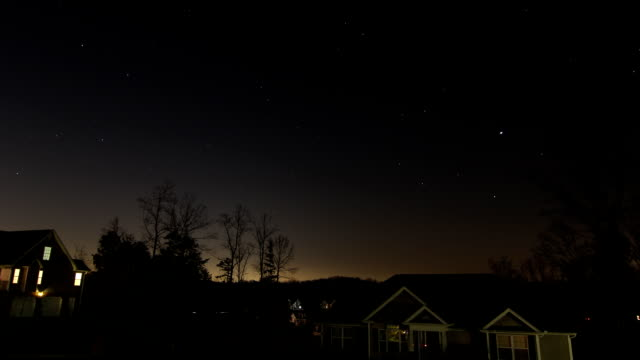 Time Lapse of Moon Rising and Stars in the Sky Over Home Buildings