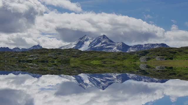 time lapse of mountain range landscape with fast moving clouds passing by - area selvatica video stock e b–roll