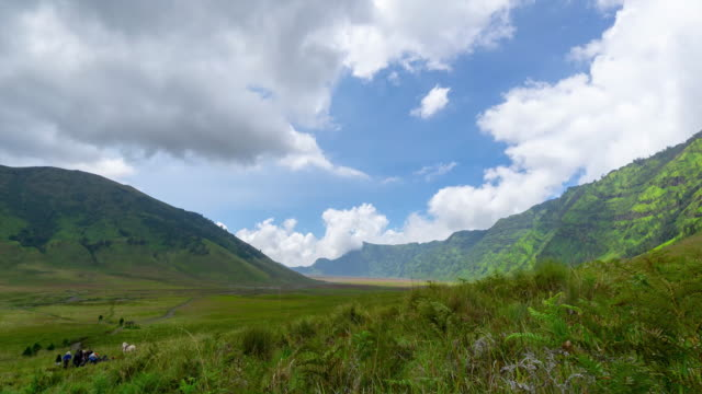 4K Time lapse of moving clouds over savannah of Bromo, a green hilly area looks green throughout the year. Zoom In.