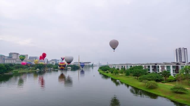 4k time lapse of moving hot balloons over lake putrajaya, malaysia. - putrajaya stock videos & royalty-free footage