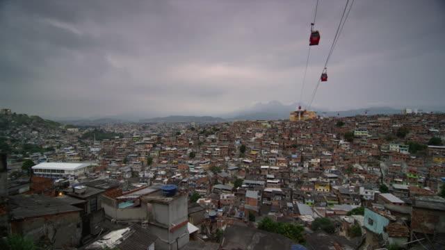 vídeos de stock e filmes b-roll de time lapse of night falling and cable cars operating above complexo do alemão favelas in rio de janiero - favela