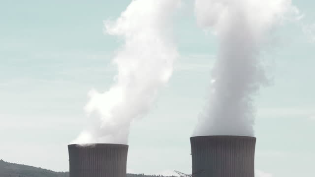 time lapse of nuclear power station with water steam chimneys and blue sky in spain. - fissione nucleare video stock e b–roll