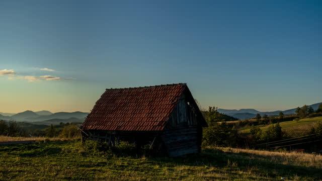 stockvideo's en b-roll-footage met time lapse van oud huis in berg bij zonsondergang en schapen op achtergrond, 4 k - sunny