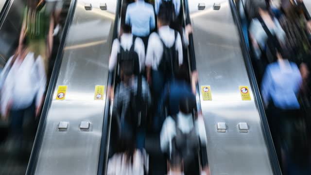 vídeos y material grabado en eventos de stock de 4k lapso de tiempo de caminata de pasajeros y turistas y correr en escalera mecánica en hora punta, estación central, hong kong - tabla de llegadas y salidas