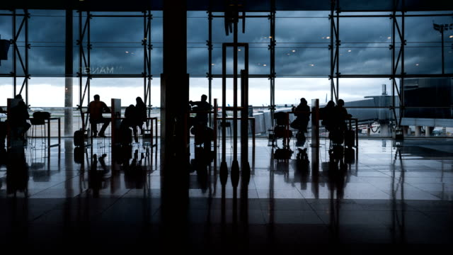 Time Lapse of passenger at Barcelona El Prat airport (silhouetted scene)