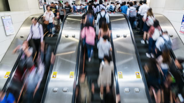 time lapse of passenger walking on escalator in rush hour - busy stock videos & royalty-free footage